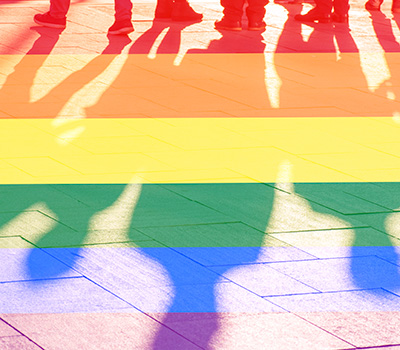 People's shadows on the ground with a rainbow color overlay