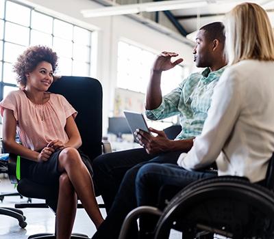 Woman sitting and speaking with a man and a woman in a wheelchair