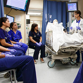 Instructor demonstrating to nursing students in a simulation lab