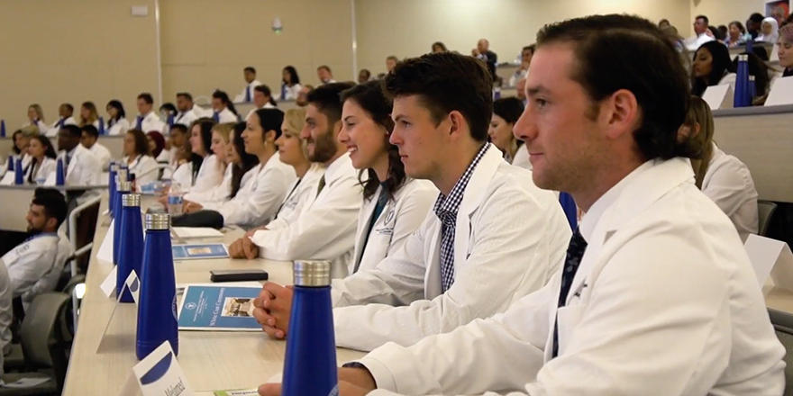 AUC Med students in a classroom wearing white coats