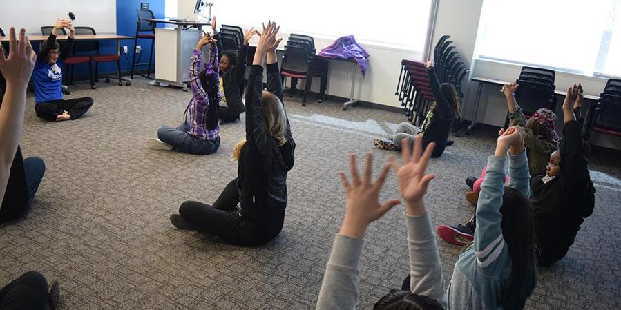 Girls in the Game participants doing yoga in a classroom