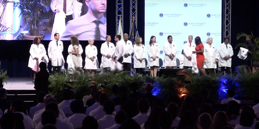 RUSM students in white coats on stage
