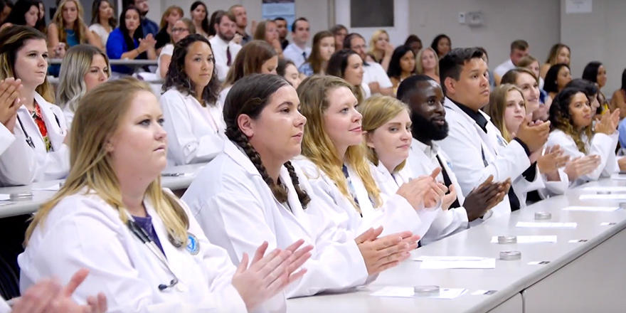 RUSVM students in a classroom wearing white coats