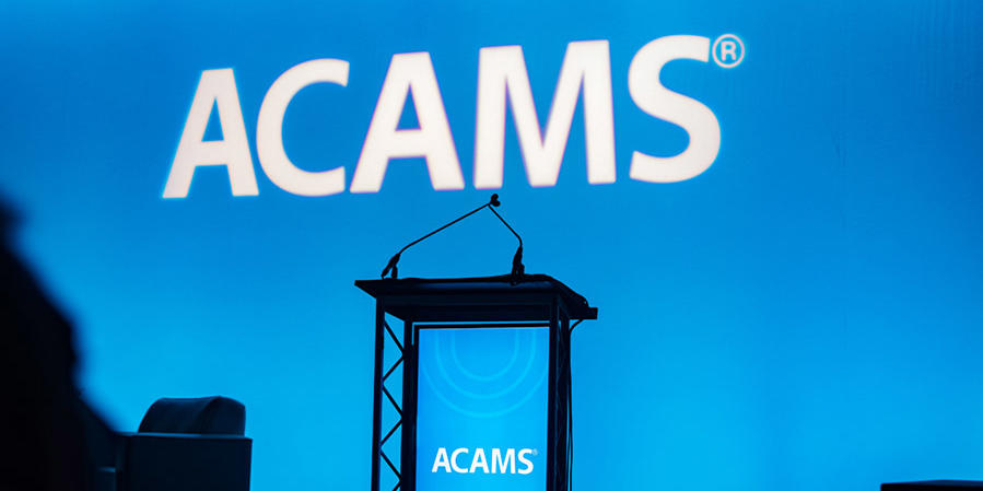 Blue-lit empty ACAMS podium at a conference