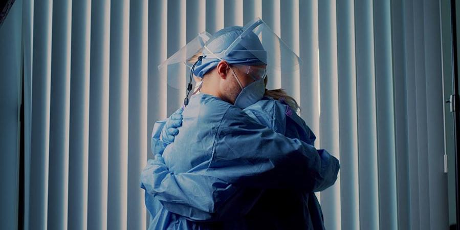 Two healthcare workers wearing PPE and hugging