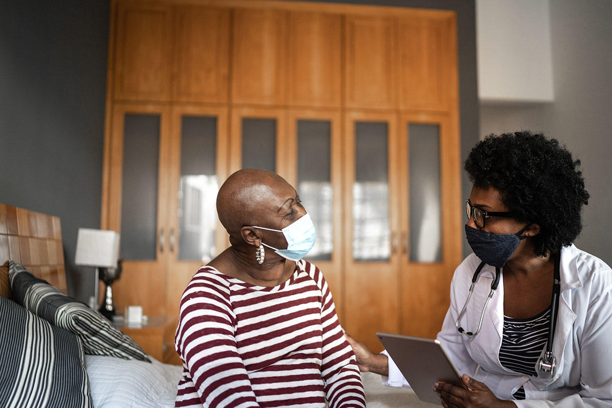 Black doctor and patient during a check up with masks