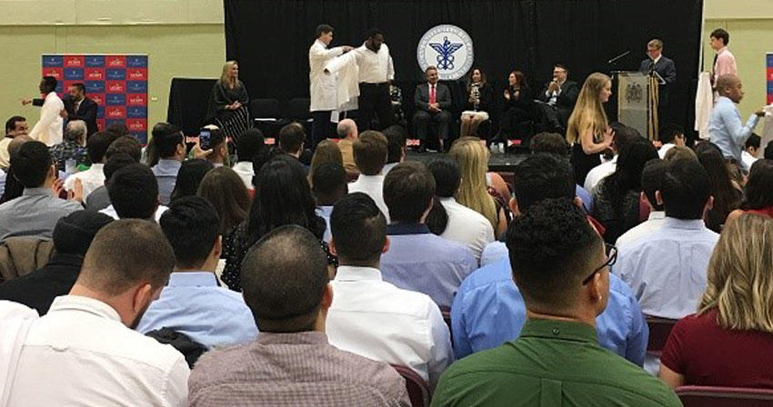 students sitting at ceremony while student on stage receives a white coat