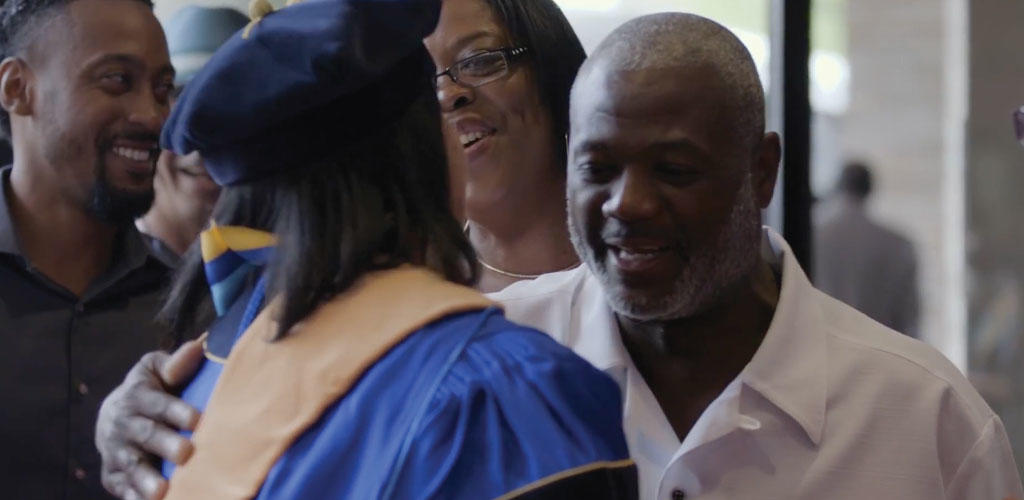 video still of graduate hugging family