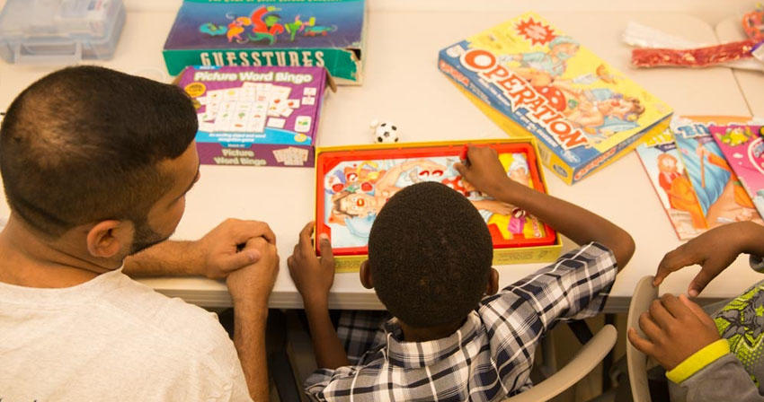 teacher playing a board game with a young student