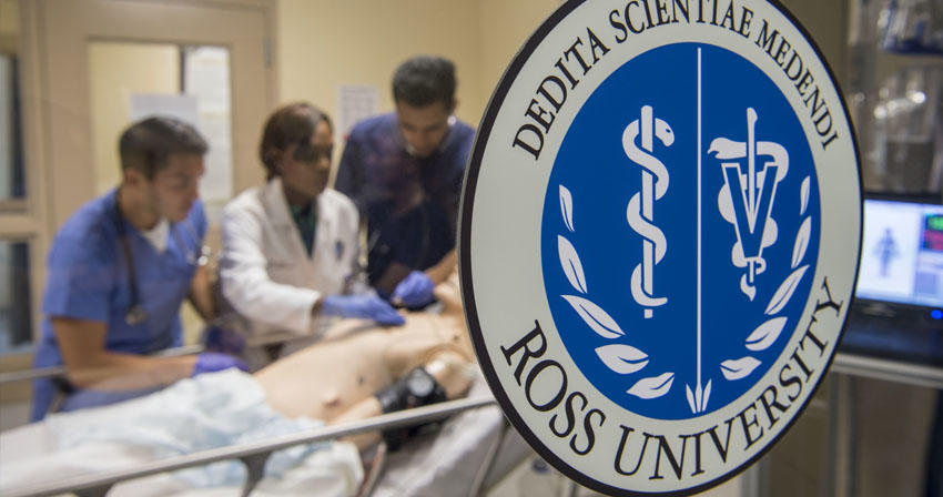 close-up of Ross U window decal with students working in a sim lab in the background